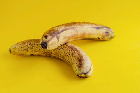 Two overripe bananas with brown spots on yellow background. Ingredients for banana bread, desserts and other dishes. Healthy eating. Selective focus. Stock fotó