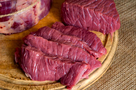 Assortment of raw beef on wooden chopping board. Piece of beef carcass round. Whole slice weighs 4 pounds and sliced in portions. Butcher's shop.