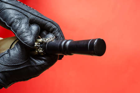 Hands in black leather glove holding an umbrella on coral background. The rain and wind protection accessory is held with two hands. Top view at an angle.