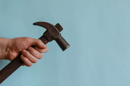 Locksmith's hand holds a vintage hammer with a claw hammer. Male hand with a hammer with a long wooden hilt. Middle-aged man of European race. Hand tool