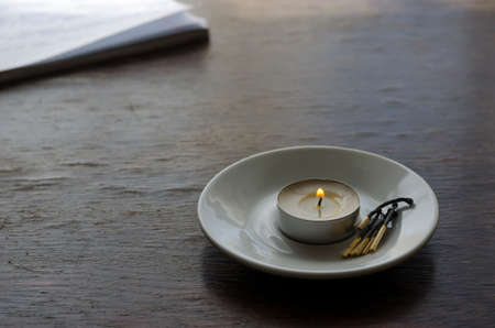 A small burning candle and a group of burnt matches in a saucer on the table. Protected candle is a symbol of memory. Side view. Copy space. Selective focus.
