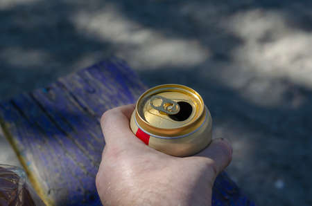 Male hand with an aluminum can of beer. Opened can of lager beer. Quenching thirst on a hot summer day. Lifestyle. Selective focus. Фото со стока
