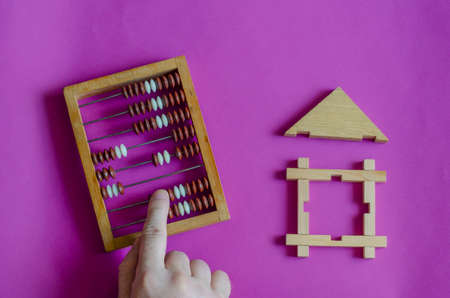 Male hand calculates an abacus next to toy wooden house on lilac background. The concept of mortgage or lending secured by real estate. View from above. Stock fotó