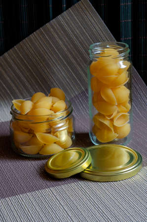 Two random glass jars of raw Conchiglie. Close-up of serving of raw pasta. Eco-friendly packaging for storing food. Side view at an angle. Selective focus.