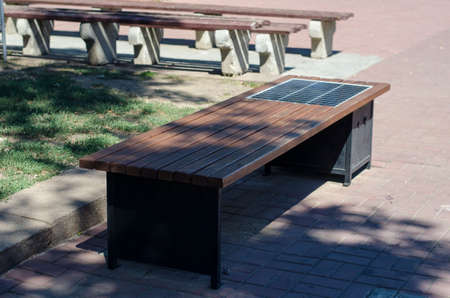 Park bench with solar panel. A row of wooden benches with the ability to charge gadgets. Alternative energy sources in everyday life. Without people.