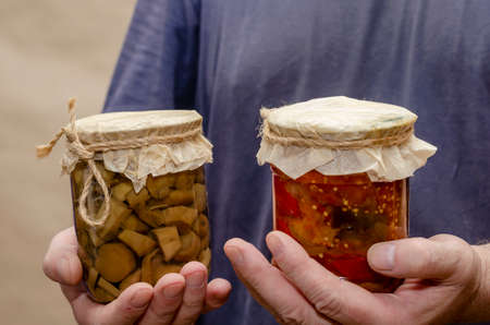 Male hands are holding glass jars of canned food. Transparent jar with lecho and mushrooms. Canned food. Selective focus.