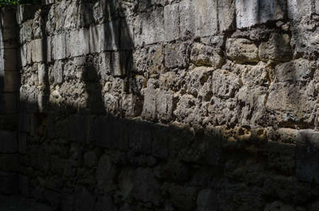 Old wall of limestone with gray seams, perspective view. Fragment of an old wall divided by sunlight and shadow. The concept of the struggle between good and evil. 写真素材