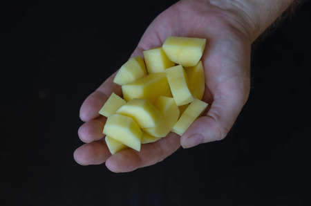 Mature man's hand holds finely chopped raw potatoes. A serving of peeled and chopped vegetables in the palm of his hand. Cooking. Selective focus.
