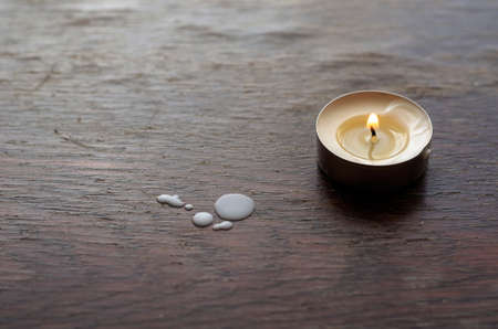 A burning candle on a wooden table. Small candle with a flame. Drops of wax on the table. Selective focus. Stockfoto