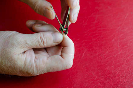 Middle-aged Caucasian man cuts his own nails. Nail clippers in male hands on a red table. Health and hygiene. Close-up.
