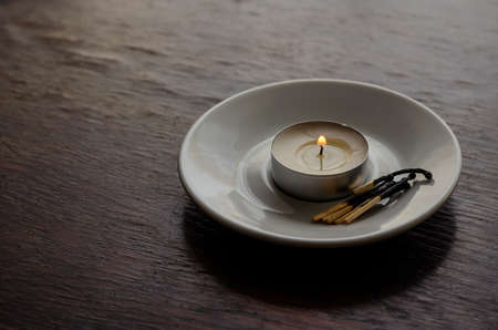 Burning candle in a white saucer on a wooden table. Several burnt matches nearby. Selective focus.