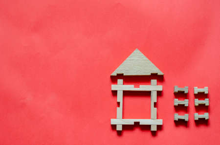 Wooden house from a children's constructor on a coral background. Simple house made of wooden geometric details. View from above. Copy space.