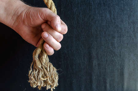 A man's hand holds a rope with a knotted knot on a dark background. A mature man with a thick rope in his hand. Active lifestyle. Selective focus.