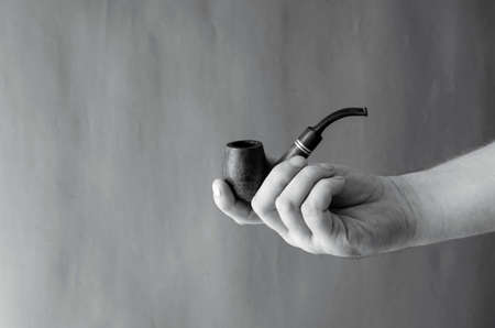 Smoking pipe in hand against the background of a textured wall. An adult male's right hand holds a smoking pipe made from heather or briar root. Monochrome photo. Selective focus.