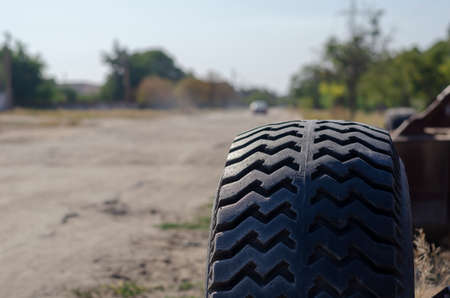 A close-up of an all-terrain wheel on the background of a dusty road. The silhouette of a retreating car in the background. Shooting from the roadside. Focus on the foreground. Foto de archivo