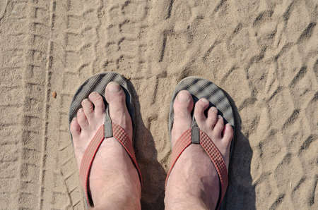 Top view of male legs in slippers. A mature man in slippers with bare feet stands on a dusty road. Feet covered with dust and dirt