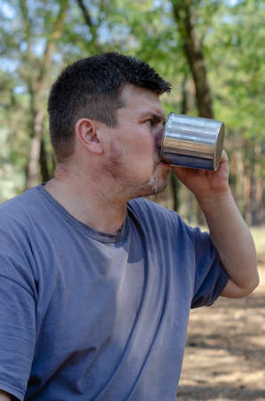 A man holds out a drink from a metal mug in the forest. A grown man with a bristle quenches his thirst .. Tourism and Active lifestyle.