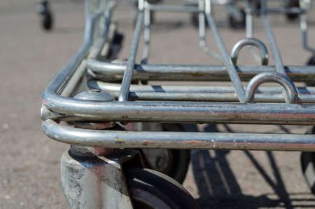 Supermarket Shopping HandCart Cart. Supermarket shopping trolleys in outdoor parking. Empty metal carts on a sunny summer day. Without anyone. Selective focus.