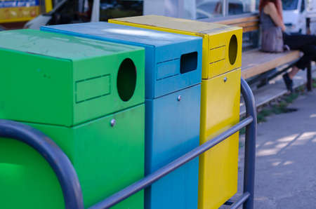 Three multi-colored garbage containers on a city street. Yellow, blue and green rectangular containers for waste separation. Ecological concept. Selective focus.