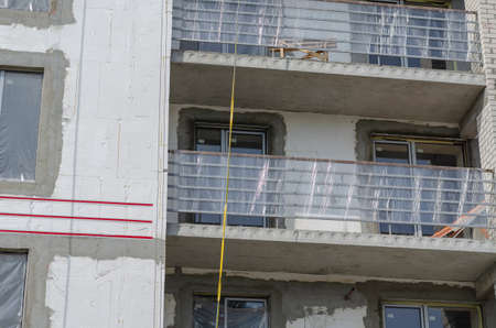 Fragment of the facade of an unfinished apartment building. Empty balconies and partially insulated outer walls of the building. Construction of a new skyscraper.