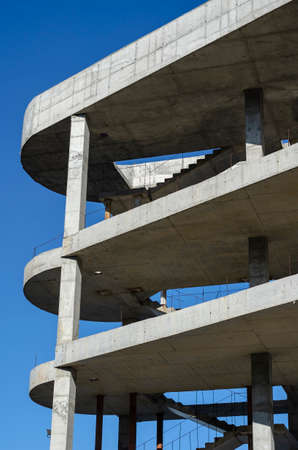 Geometric shape made of concrete on a background of blue sky. Unfinished building of a modern shopping center. Industrial background.