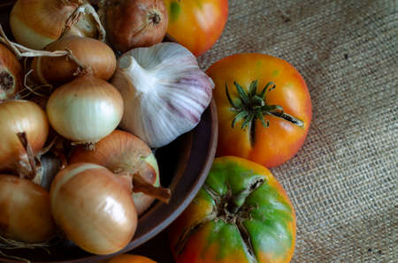 Yellow tomatoes, onions and garlic on burlap. Harvest of autumn vegetables. The result of farm labor. Harvest Festival. Part of a series.