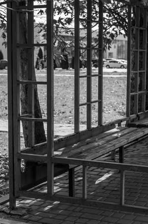 Empty bus stop with wooden benches. Black and white photo of a suburban bus stop. Public transport. Travel concept. Without anyone