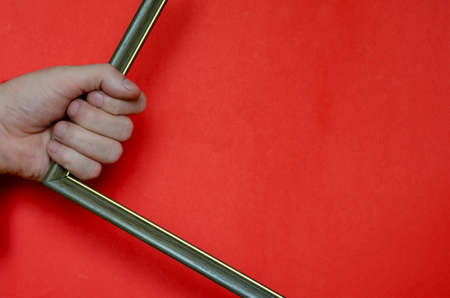 A male hand is holding an empty photo or picture frame on a red background. Bold multitasking background for various tasks with copy space. Minimalism. 版權商用圖片