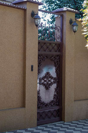 Metal entrance door and a high fence with video surveillance camera. Entrance to the territory of private household. Without anyone Reklamní fotografie