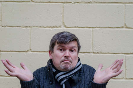 Portrait of a surprised man with his hands divorced from the side. Middle-aged grayish man expresses surprise against yellow wall background.
