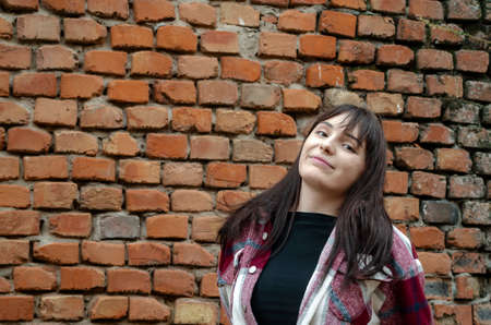 Portrait of a young woman with a pensive look. Beautiful woman with flowing long hair against a brick wall background. Copy space