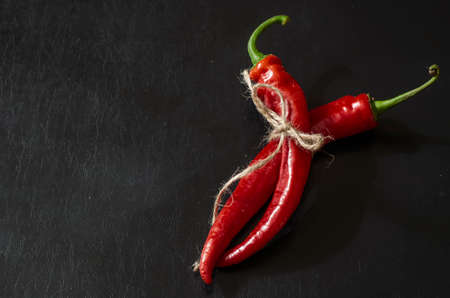 Two pods of ripe red chili peppers on black background. Freshly plucked from vegetable patch and tied with twine. New crop of hot peppers.