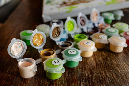 Active leisure at home, creative hobby concept. Set of small plastic containers with acrylic paints for drawing. Numbered paints. Drawing by numbers.