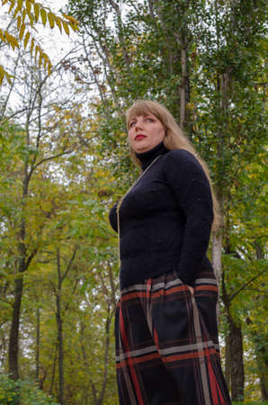 Portrait of middle-aged woman with blond dissolved hair in an autumn park.