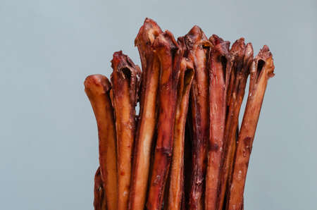 Air dried bull penises for dogs on a blue background. Group of natural chewing treats for dogs. Bully sticks 版權商用圖片