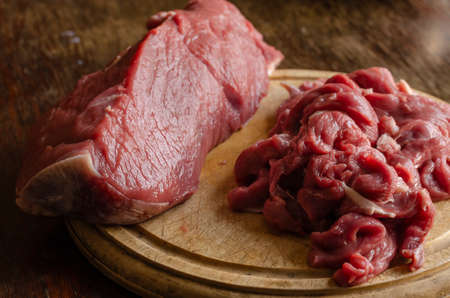 Pieces of raw beef on a round cutting board. Whole pieces of beef tenderloin and shredded into strips for Befstrogonovs