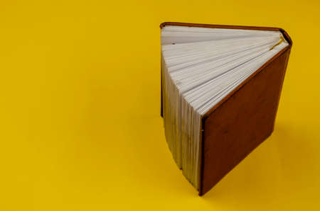Old diary in brown leather binding stands on endpaper on yellow background. A diary with dirt and embossing on the cover.