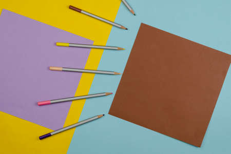Geometric composition with color pencils on the multicolor background. Emphasis on the brown square. Copy space. Top view, Flat lay Stock Photo