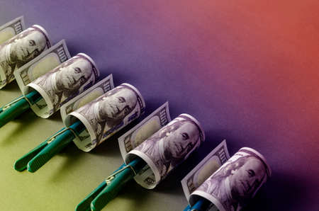 Creative abstract background with one hundred dollar bills and clothespins on a multicolored spectral background. A group of banknotes twisted into a cylinder. Close-up, selective focus. Stockfoto