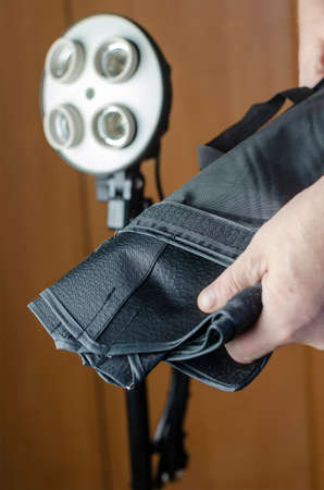 Man Hands takes the reflector for the softbox out of its case. Studio lighting assembly sequence. Softbox, continuous lighting, photo equipment.