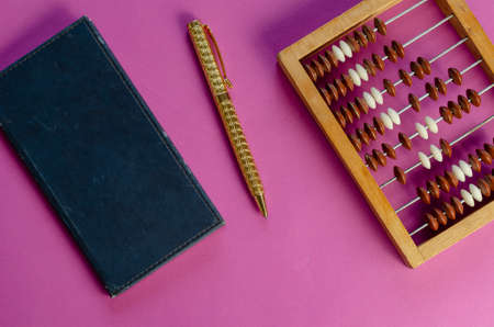Old notebook, wooden abacus and a gold-colored pen on a pink background. Scratched leather notebook. Top view, flat lay.