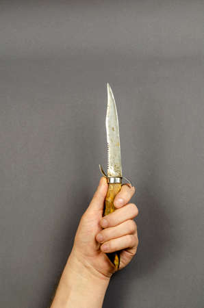 Hand holds a hunting knife on a gray background. Old Goat's leg knife with a guard. Side view. Copy space