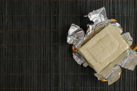Rectangular piece of processed cheese in open foil package on a dark bamboo background. Cheese ready to eat. Dairy products, food.