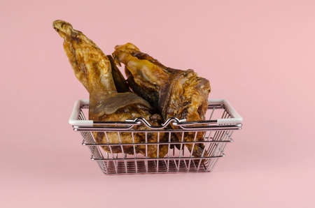 Shopping basket with dog treats on a pink background. Chewy treats in metal basket. Dried beef ears for pets. Pet supplies. Side view from an angle.