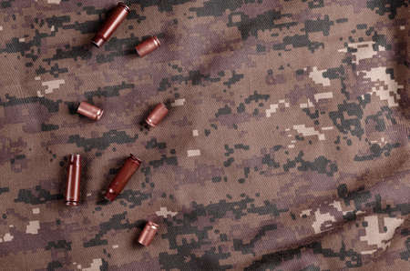 A few random casings on camouflage cloth. A group of pistol and rifle empty casings lie on military uniforms. Army theme.