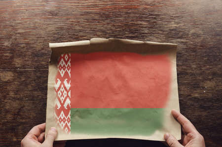 The red-green flag of the Republic of Belarus on old tattered paper. A man's hands press an unfolded sheet of parchment against a brown wooden table. View from above