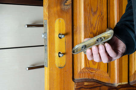 A man removes an old mortise lock on a wooden interior door. The hand holds the overlay bar of the lock with the door handle. Furniture hardware repair or replacement services. Indoors.