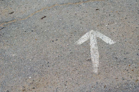 A hand-drawn white arrow on the asphalt. The sign indicates a crack in the pavement. The old Crack is clogged with sand and dirt. View from above from an angle. Selective focus.