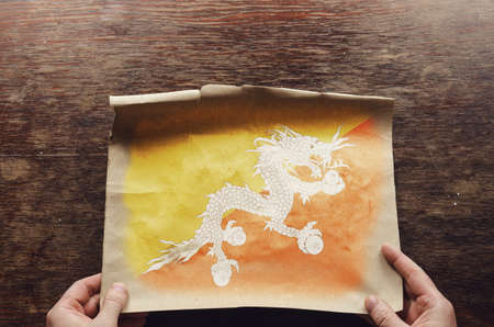 The national flag of Bhutan on a torn piece of paper. A man's hands press an unfolded sheet of parchment to a brown wooden table. View from above