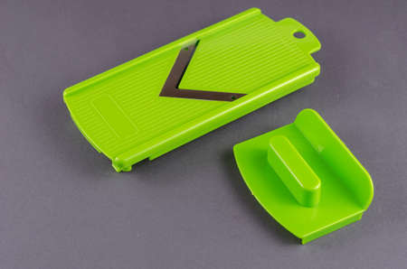 Sharpening and cutting pusher for vegetable slicer on gray background. Green plastic fixture for safely slicing vegetables, fruits, cheeses and other products. Kitchen Accessories